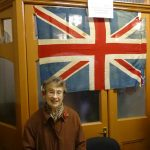 Miss Jean Linnard standing beneath the flag her grandparents flew on 11th November 1918 in Christopher Road