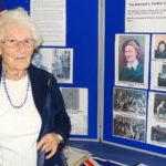 Mrs Reida Francis standing next to the display of her work with the Women's Timber Corps in WW2