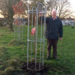 Bill standing next to the newly planted tree